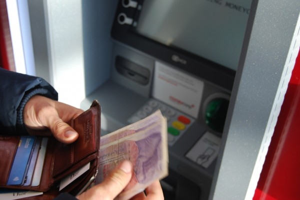 person holding brown leather wallet and banknotes at the atm