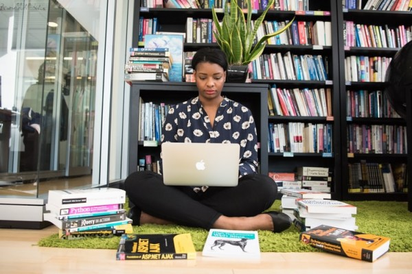 An entrepreneur sitting down surrounded by books while using MacBook